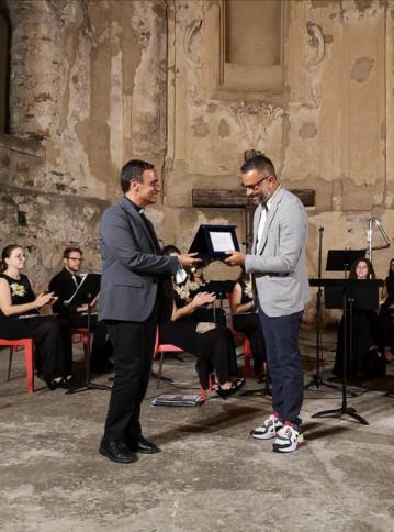 Don Francesco Cristofaro volto noto di Padre Pio TV consegna il premio all'artista Massimiliano Ferragina